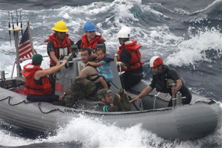 Sailors from Oliver Hazard Perry-class frigate USS Vandegrift assist in the rescue of a family with a sick infant via the ship's small boat as part of a joint U.S. Navy, Coast Guard and California Air National Guard rescue effort as seen in this U.S. Navy handout photo taken in the Pacific Ocean on April 6, 2014. REUTERS/U.S. Navy Photo/Handout via Reuters