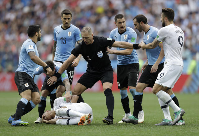 Uruguay players protest to referee Nestor Pitana of Argentina that France's Kylian Mbappe, on the ground, is overreacting after taking a dive during the quarterfinal match between Uruguay and France at the 2018 soccer World Cup in the Nizhny Novgorod Stadium, in Nizhny Novgorod, Russia, Friday, July 6, 2018. (AP Photo/Natacha Pisarenko)