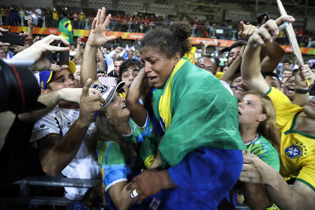 <p>Brazil's Rafaela Silva, centre, celebrates after winning the gold medal of the women's 57-kg judo competition at the 2016 Summer Olympics in Rio de Janeiro, Brazil, Monday, Aug. 8, 2016. (AP Photo/Markus Schreiber) </p>
