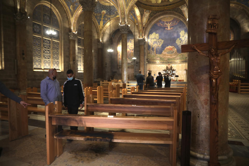 "A burned pew is seen at the Church of All Nations in the Garden of Gethsemane, in east Jerusalem, Friday, Dec. 4, 2020. Israeli police said Friday they arrested a Jewish man after he poured out a ""flammable liquid"" inside a church near Jerusalem's Old City, in what they described as a ""criminal"" incident. (AP Photo/Mahmoud Illean)"