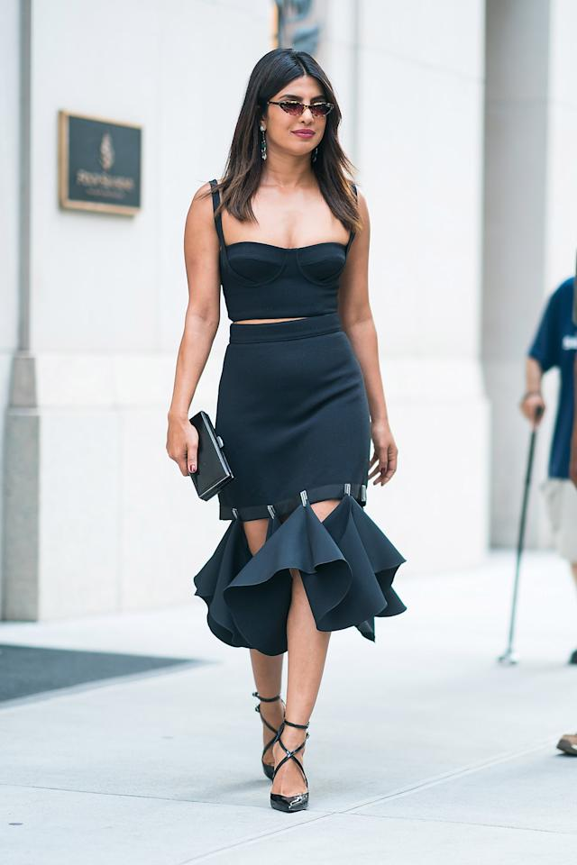"""<p>Wearing a <a rel=""""nofollow"""" href=""""https://www.popsugar.com/fashion/Priyanka-Chopra-Black-Cutout-Dress-Daily-Front-Row-Awards-45237905"""">black Dion Lee bustier and matching midi skirt</a> with strappy patent leather heels.</p>"""