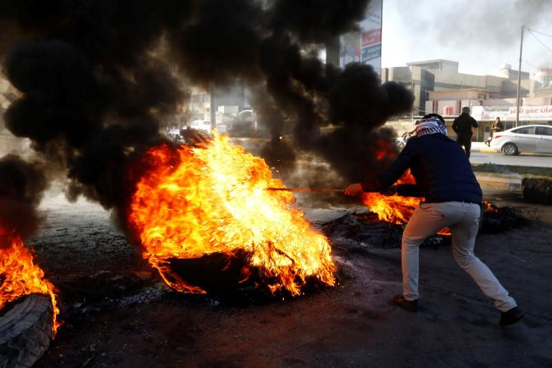 An Iraqi demonstrator burns tires to block a road during ongoing anti-government protests in Najaf