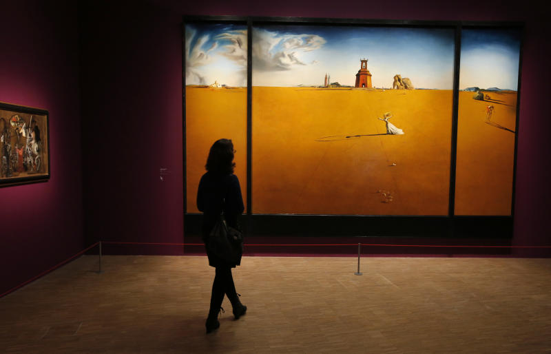 """In this photo taken Monday Nov. 19, 2012, a women looks at the painting 'Paysage avec jeune fille sautant a la corde, 1936' by Spanish artist Salvador Dali (1904-1989) during the presentation to the press of the exhibition """"Dali"""" at the Centre Pompidou modern art museum, in Paris. A major retrospective of Salvador Dali in Paris aims to rewrite the art history books, reconciling for the first time the last decades of his life _ when he was accused of money-making self-publicity through numerous television appearances _ with his earlier, respected Surrealist period. (AP Photo/Francois Mori)"""