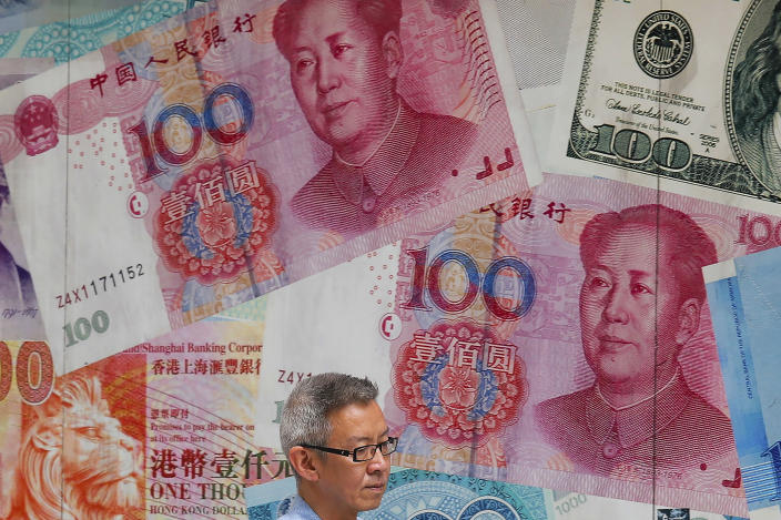 In this Tuesday, Aug. 6, 2019, photo, a man walks by a money exchange shop decorated with Chinese yuan banknotes and other countries currency banknotes at Central, a business district in Hong Kong. China's yuan has weakened again after signs its decline was stabilizing helped to reassure financial markets. (AP Photo/Kin Cheung)