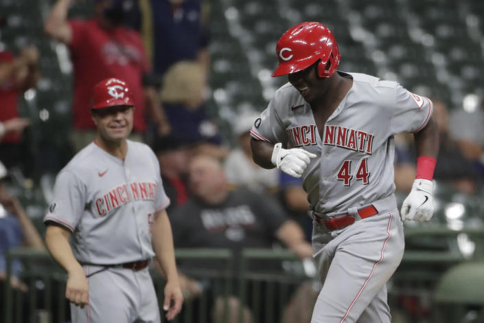 Cincinnati Reds' Aristides Aquino (44) smiles with third base coach J.R. House after hitting a two-run home run during the ninth inning of a baseball game against the Milwaukee Brewers, Monday, June 14, 2021, in Milwaukee. (AP Photo/Aaron Gash)