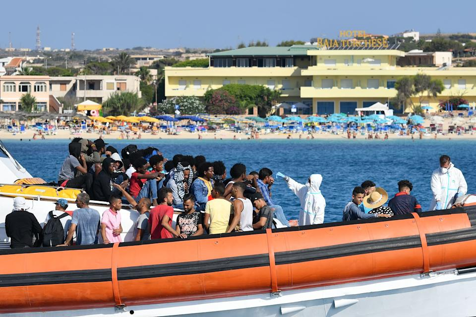 Migrants from Tunisia and Lybia are examined as they arrive onboard of an Italian Guardia Costiera (Coast Guard) boat in the Italian Pelagie Island of Lampedusa on August 1, 2020. (Photo by Alberto PIZZOLI / AFP) (Photo by ALBERTO PIZZOLI/AFP via Getty Images) (Photo: ALBERTO PIZZOLI via Getty Images)