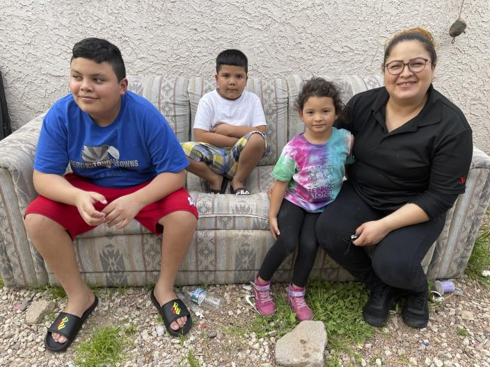 Silvia Baca Garcia, 33, sits outside her home she shares with her three children and two grandchildren in Phoenix, on Thursday, March 25, 2021. From left are her sons, Hugo, 14, and Adrian, 6, and granddaughter, Sofia. Originally from Honduras, Baca Garcia says she struggled to feed her family when she was out of work for months during the coronavirus pandemic. She said she's relieved that her two school-aged sons are now back on campus, where they each get two hot meals every day they go to class. (AP Photo/Anita Snow)
