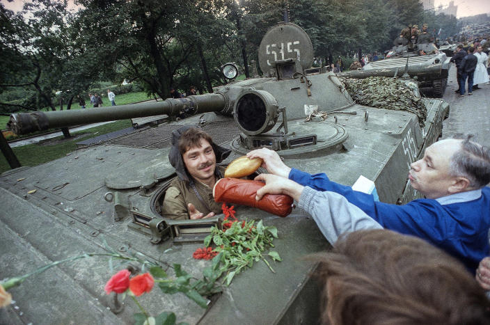 FILE - In this Wednesday, Aug. 21, 1991 file photo, appreciative muscovites hand bread, sausages and flowers to a Soviet tank's driver who helped stop the failed hardline coup in Moscow, Russia. When a group of top Communist officials ousted Soviet leader Mikhail Gorbachev 30 years ago and flooded Moscow with tanks, the world held its breath, fearing a rollback on liberal reforms and a return to the Cold War confrontation. But the August 1991 coup collapsed in just three days, precipitating the breakup of the Soviet Union that plotters said they were trying to prevent.(AP Photo/Czarek Sokolowski, File)