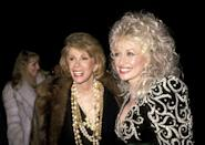 "<p>Dolly smiles with Comedian Joan Rivers. She would later write <a href=""https://twitter.com/dollyparton/status/507650070469431296?lang=en"" rel=""nofollow noopener"" target=""_blank"" data-ylk=""slk:of her friend's death"" class=""link rapid-noclick-resp"">of her friend's death</a>, ""Though her death is no laughing matter, Joan Rivers' life was nothing but. I know she would want us all to keep smiling. And I know we always will when we think of her.""</p>"