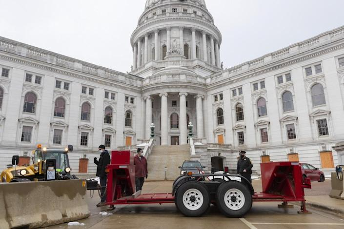 Workers set up a vehicle barricade on one side of the Capitol in Madison, Wis.