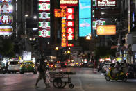 A vegetable vendor pushes his cart across a street in China town in Bangkok, Thailand, on Aug. 3, 2021. As Thailand battles a punishing COVID-19 surge with nearly 20,000 new cases every day, people who depend on tourism struggle in what was one of the most-visited cities in the world, with 20 million visitors in the year before the pandemic. (AP Photo/Sakchai Lalit)