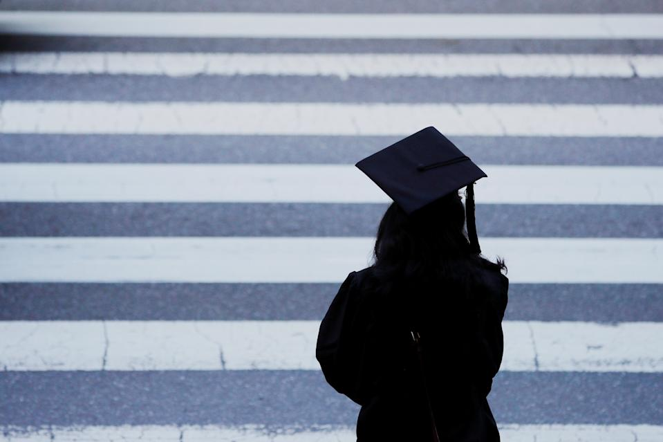A graduating student waits to cross the street before Commencement Exercises at the Massachusetts Institute of Technology (MIT) in Cambridge, Massachusetts, U.S., June 7, 2019.   REUTERS/Brian Snyder