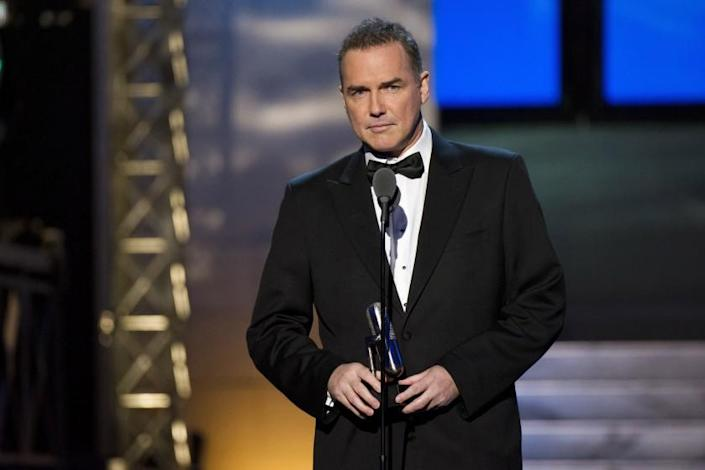 A man in a tuxedo standing before a microphone on a stage
