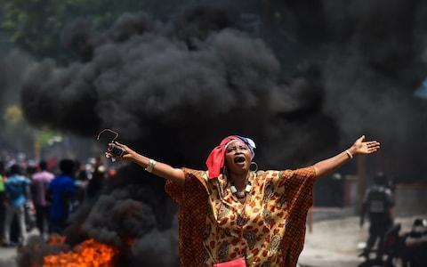 A demonstrator holds up her arms and chants slogans during a protest against the ruling government in Port-au-Prince in June - Credit: CHANDAN KHANNA/AFP/Getty Images