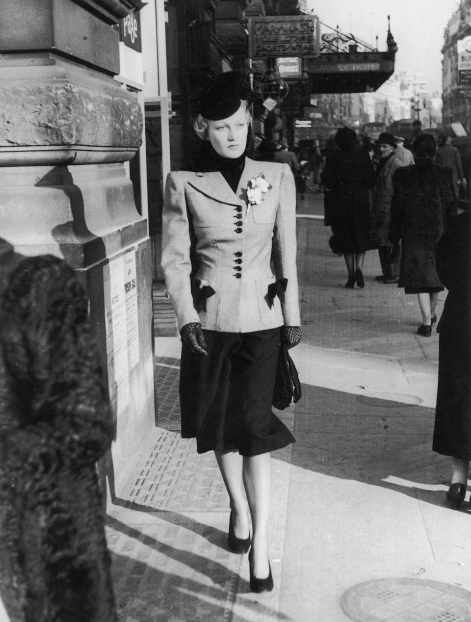 <p>A smartly dressed woman walks down a London street. Her tailored suit has squared shoulders, and the contrasting buttons and trim on her jacket match the just-below-the-knee skirt. </p>
