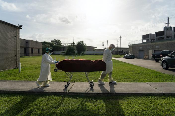Medical staff wearing full PPE push a stretcher with a deceased patient to a car outside the COVID-19 intensive care unit at the United Memorial Medical Center in Houston, Texas, on June 30, 2020.