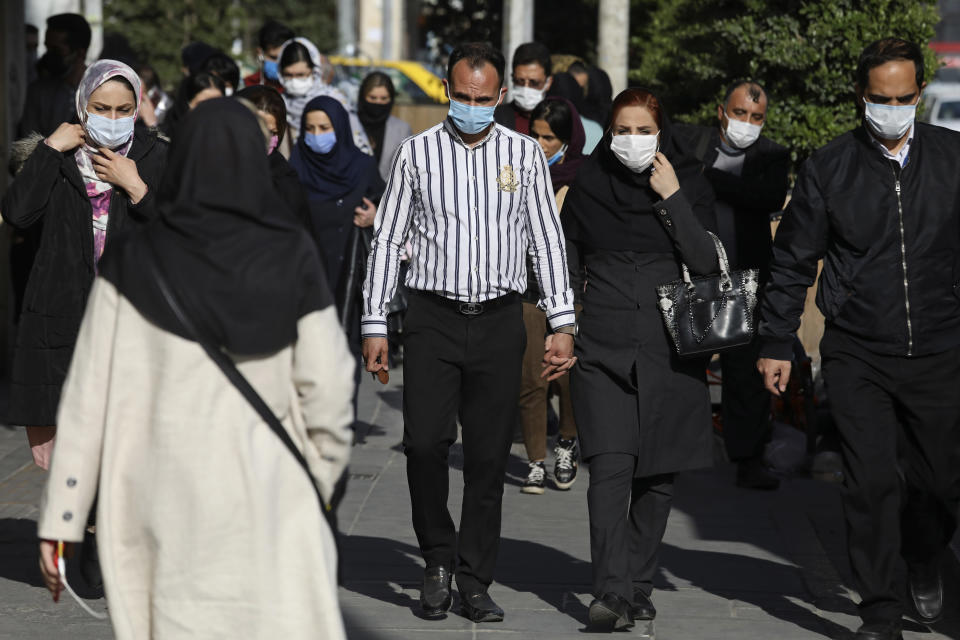 FILE - In this April 5, 2021, file photo, people wearing protective face masks to help prevent the spread of the coronavirus walk in downtown Tehran, Iran. Nations around the world set new records Thursday, April 8, for COVID-19 deaths and new coronavirus infections, and the disease surged even in some countries that have kept the virus in check. Iran set a new coronavirus infection record Thursday for the third straight day, reporting nearly 22,600 new cases. (AP Photo/Vahid Salemi, File)