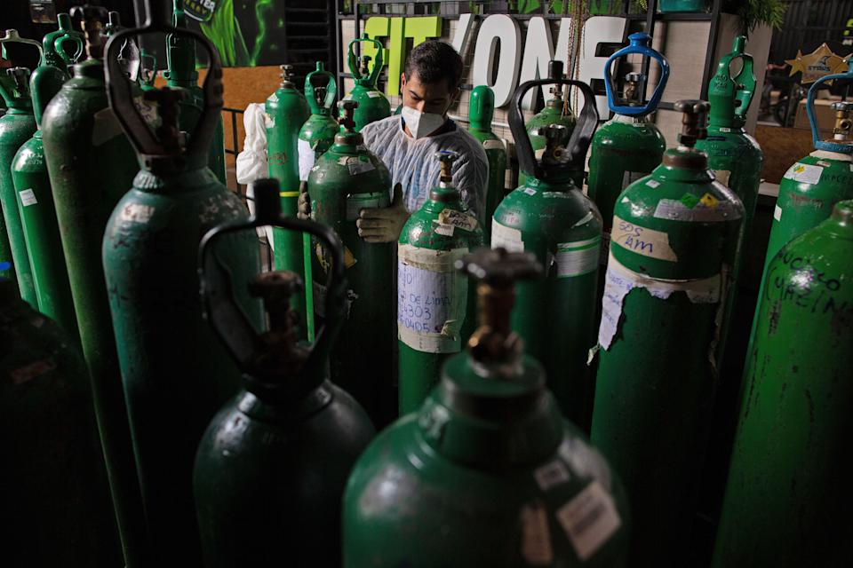 Volunteers from the SOS medical emergency services refill oxygen tanks for free, in Manaus, Brazil on January 30, 2021. - As a new pandemic wave hits Latin America, the region with the second highest number of deaths from COVID-19 in the world, the same scene of desperation repeats itself: people queueing in long lines or paying exorbitant prices for an oxygen tank, while the sick die of asphyxiation in hospitals. (Photo by MICHAEL DANTAS / AFP) (Photo by MICHAEL DANTAS/AFP via Getty Images)