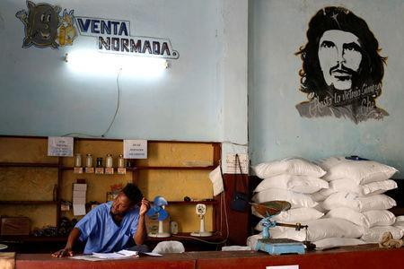 """A man works in a subsidised state store, or """"bodega"""", next to an image of late revolutionary hero Ernesto """"Che"""" Guevara in Havana, Cuba July 21, 2018. REUTERS/Stringer"""