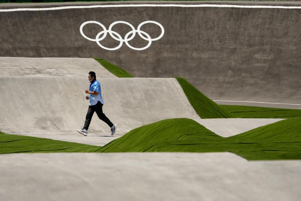 A worker runs across the BMX racing track as preparations continue for the 2020 Summer Olympics, Tuesday, July 20, 2021, at the Ariake Urban Sports Park in Tokyo. (AP Photo/Charlie Riedel)