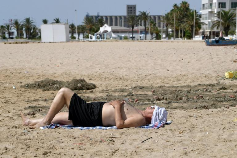 A man lies on a nearly deserted beach during a lockdown was imposed by the Tunisian authorities as a measure against the spread of coronavirus pandemic (AFP/FETHI BELAID)