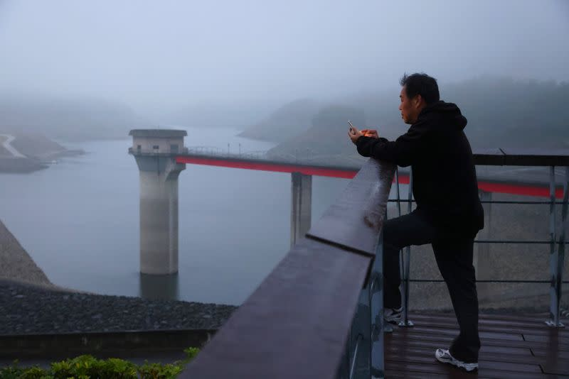 Man uses his phone in front of the Baoshan second reservoir amid low water levels during an island-wide drought, in Hsinchu, Taiwan