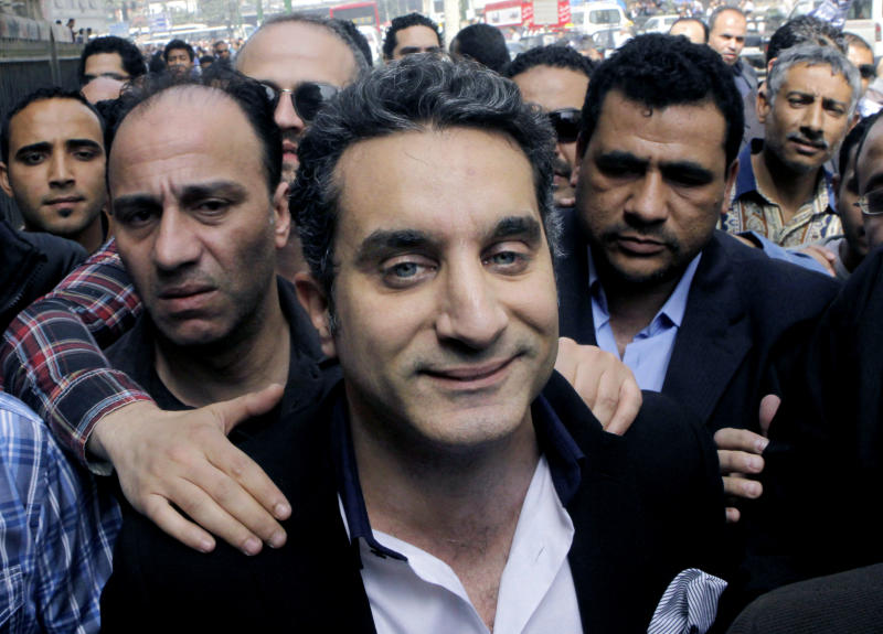 """FILE - In this Sunday, March 31, 2013 file photo, a bodyguard secures popular Egyptian television satirist Bassem Youssef, who has come to be known as Egypt's Jon Stewart, as he enters Egypt's state prosecutors office to face accusations of insulting Islam and the country's Islamist leader in Cairo, Egypt. After more than four months away, the man known as """"Egypt's Jon Stewart"""" returns the airwaves Friday in a country radically different from the one he previously mocked. Satirist Bassem Youssef's weekly """"El-Bernameg,"""" or """"The Program"""" in Arabic, mocked the country's first elected Islamist president and his supporters for mixing religion and politics, took them to task for failing to be inclusive or deliver on people's demands for change_ to the extent that some said he was one of the main reasons people turned against Mohammed Morsi. (AP Photo/Amr Nabil, File)"""