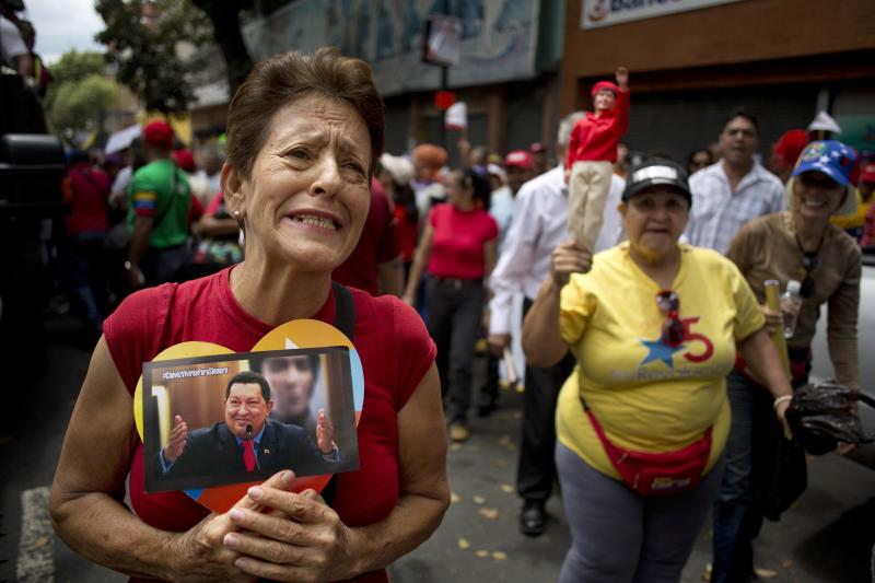 A woman chants pro-government slogans and holds a heart-framed photograph of Venezuela's late President Hugo Chavez at a rally attended by elderly people in Caracas, Venezuela, Sunday, Feb. 23, 2014. The march for peace was organized by the government and ended at Miraflores presidential palace where the marchers met with Venezuela's President Nicolas Maduro. (AP Photo/Rodrigo Abd)