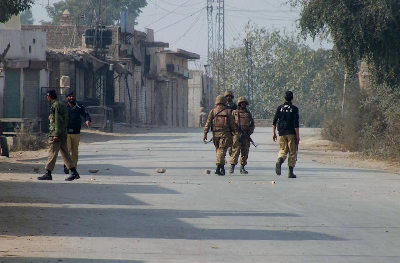 Pakistani police and army soldiers stand guard on a road leading to the site of bomb explosion in Bannu, Pakistan on Sunday Jan. 19, 2014. A regular Sunday morning troop rotation going into the Pakistani tribal region of North Waziristan was shattered by an explosion that killed tens of people, mostly paramilitary troops. The Pakistani Taliban claims responsibility for placing the bomb on one of the trucks hired for the job. (AP Photo/Ijaz Muhammad)