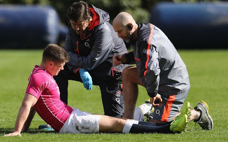 Owen Farrell, the England centre, receives attention from England physio Phil Pask (R) and Rob Young, the team doctor during the England training session at Pennyhill Park on March 9, 2017 - 2017 Getty Images