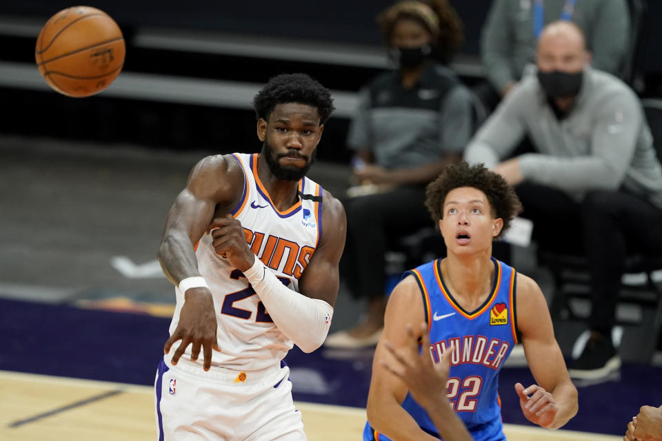 Phoenix Suns center Deandre Ayton passes as Oklahoma City Thunder forward Isaiah Roby, right, defends during the second half of an NBA basketball game, Wednesday, Jan. 27, 2021, in Phoenix. (AP Photo/Matt York)