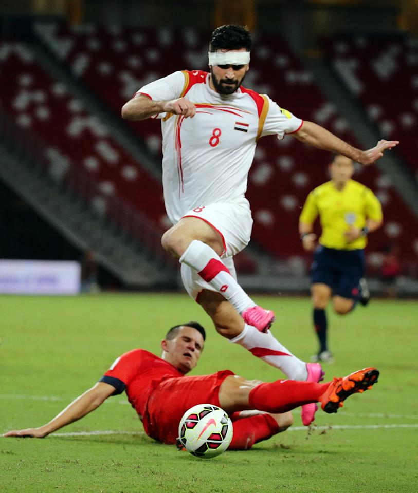 Football - Singapore v Syria - 2018 FIFA World Cup Qualifying - AFC Second Round - Group E - National Stadium, Singapore - 17/11/15 Syria's Omar Kharbin in action with Singapore's Baihakki Khaizan Action Images via Reuters / Jeremy Lee Livepic EDITORIAL USE ONLY.