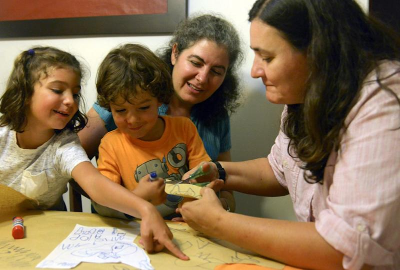 Colombian lesbian couple Ana Elisa Leiderman (2nd R) and Veronica Botero (R) watch as their daughter Raquel, 6, points at a sketch done by their son Ari, 4, both conceived by artificial insemination, at home in Medellin, Colombia, on August 26, 2014