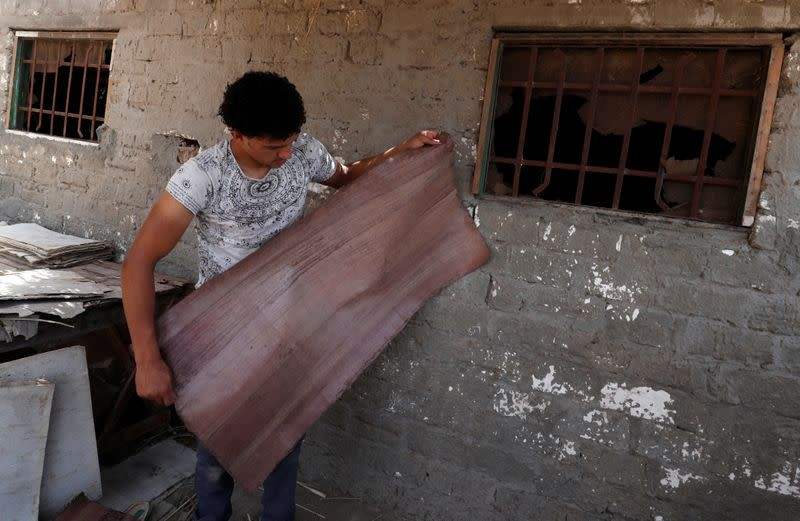 Mohamed Abdul Rahman, 18, checks sheets if papyrus is dry at a workshop in al-Qaramous village