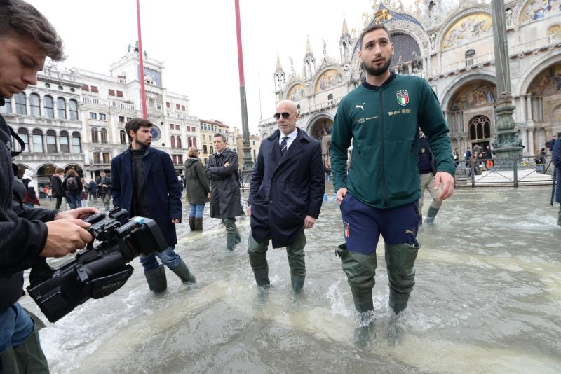 Italy's goalkeeper Gianluigi Donnarumma, and team manager Gianluca Vialli are seen in St. Mark's Square during a solidarity visit to Venice following the exceptional high water that brought the city to its knees, in Venice, northern Italy, Saturday, Nov. 16, 2019. Four days ago, the Italian lagoon city experienced its worst flooding in more than 50 years. (Andrea Merola/ANSA via AP)