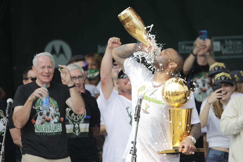 Milwaukee Bucks' P.J. Tucker drinks Champagne as he holds the NBA Championship Trophy during a parade celebrating the basketball team's NBA Championship win, Thursday, July 22, 2021, in Milwaukee. (AP Photo/Aaron Gash)