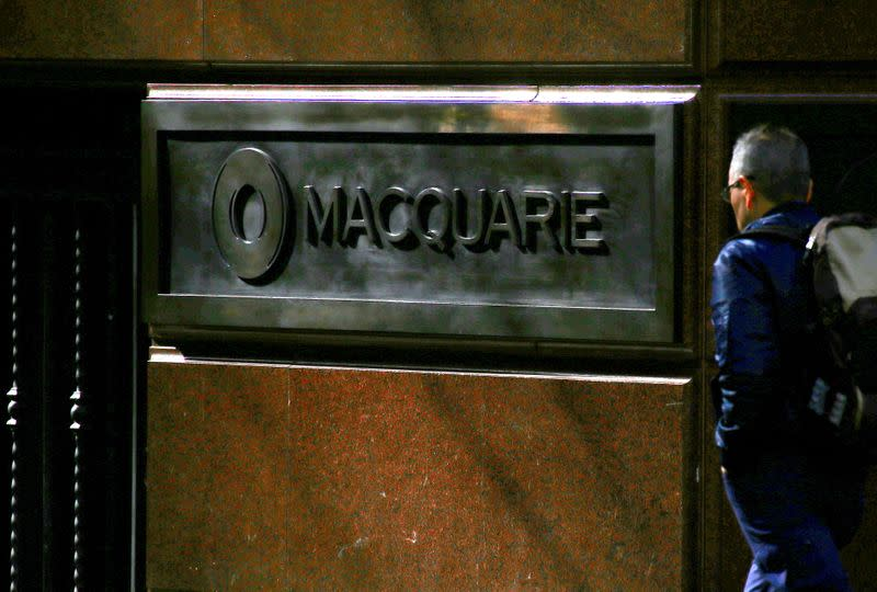 FILE PHOTO: A pedestrian walks past the logo of Australia's biggest investment bank Macquarie Group Ltd which adorns a wall on the outside of their Sydney office headquarters in central Sydney, Australia