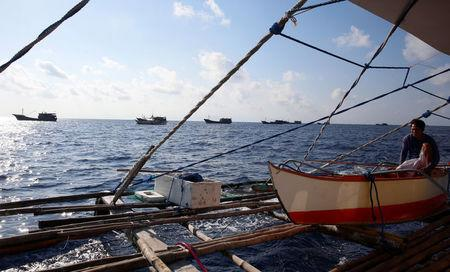 A Philippine fisherman rests on a dinghy as Chinese fishing boats pass by at the disputed Scarborough Shoal