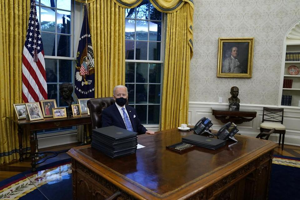 Biden signs his first executive orders in the Oval Office.