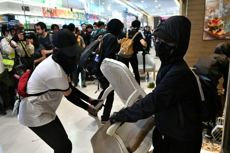 Hong Kong activists and police have clashed in multiple neighbourhoods after protesters held flashmob protests and vandalism sprees inside malls (AFP Photo/Anthony WALLACE)