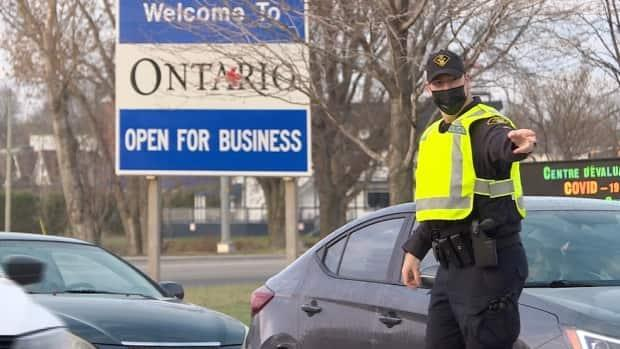 An Ontario Provincial Police (OPP) officer speaks to drivers crossing the Long-Sault Bridge from Grenville-sur-la-Rouge, Que., to Hawkesbury, Ont., April 19, 2021, the first day of border checkpoints on Ontario's provincial borders. (Denis Babin/Radio-Canada - image credit)