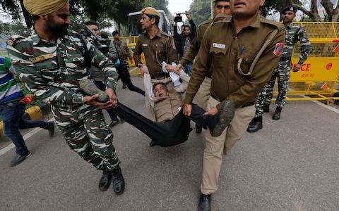 Police detain a demonstrator during a protest against the attack on a bus that killed 44 CRPF personnel in south Kashmir on Thursday - Credit: Reuters
