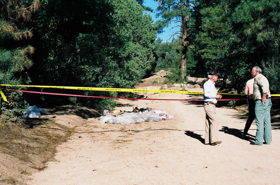 This undated photo provided by the Yavapai County Sheriff's Office shows authorities at the site outside Prescott, Ariz., where Pamela Pitts' body was found in 1988 among a pile of trash. Pitts' then-roommate, Shelly Harmon, recently confessed to killing her and was sentenced to time she already had served in another killing. (Yavapai County Sheriff's Office via AP)