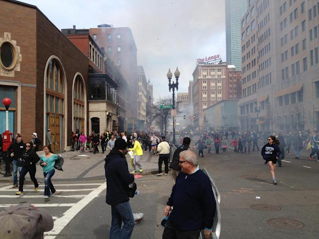 This Monday, April 15, 2013 photo shows a man who was dubbed Suspect No. 2 in the Boston Marathon bombings by law enforcement, on the left side of the frame, wearing a white baseball cap, walking away from the scene of the explosions. The FBI identified him as 19-year-old college student Dzhokhar Tsarnaev, who along with his brother Tamerlan, 26, previously known as Suspect No. 1, killed an MIT police officer, severely wounded another lawman and hurled explosives at police in a car chase and gun battle during a night of violence, early Friday, April 19, 2013. Tamerlan Tsarnaev was killed overnight, officials said, while his brother Dzhokhar remains at large. (AP Photo/David Green)