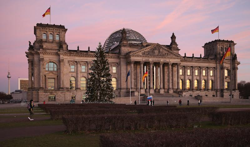 BERLIN, GERMANY - DECEMBER 16: The Reichstag, seat of the Bundestag, stands under a twilight sky on the day Angela Merkel, Chancellor and Chairwoman of the German Christian Democrats (CDU), Horst Seehofer, Chairman of the Bavarian Christian Democrats (CSU) and Sigmar Gabriel, Chairman of the German Social Democrats (SPD), signed the coalition agreement between the three parties that seals their cooperation and allows the creation of a new German coalition government on December 16, 2013 in Berlin, Germany. The new government is scheduled to be sworn in tomorrow. (Photo by Sean Gallup/Getty Images)