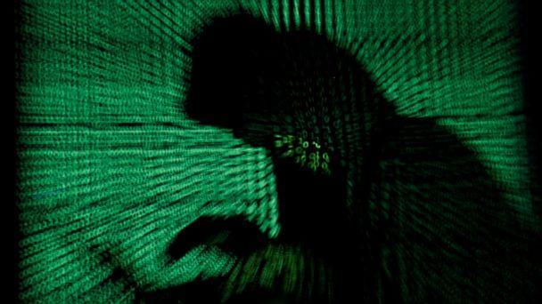 PHOTO: A hooded man holds a laptop computer as cyber code is projected on him in this illustration picture taken on May 13, 2017. (Kacper Pempel/Reuters, FILE)