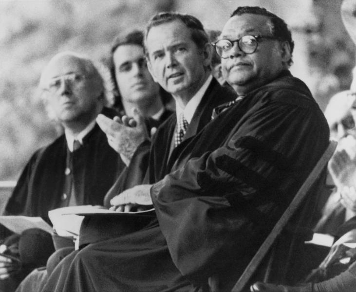 FILE - In this Monday, May 17, 1976 file photo, U.S. Dept. of Transportation Secretary William T. Coleman Jr., right, and Michigan Gov. William G. Milliken, second from right, sit on the platform during Commencement ceremonies at Yale University in New Haven, Conn. William G. Milliken, Michigan's longest-serving governor who established a record of environmental conservation and bipartisan cooperation that made him popular among Republicans and Democrats, died Friday, Oct. 18, 2019 at age 97, a family spokesman said. (AP Photo/Bob Child, File)