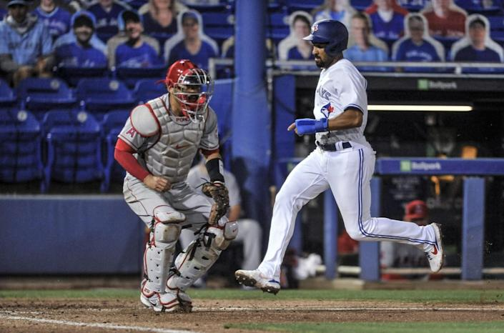 Angels catcher Kurt Suzuki waits for the throw as the Blue Jays' Marcus Semien scores in the fourth inning.