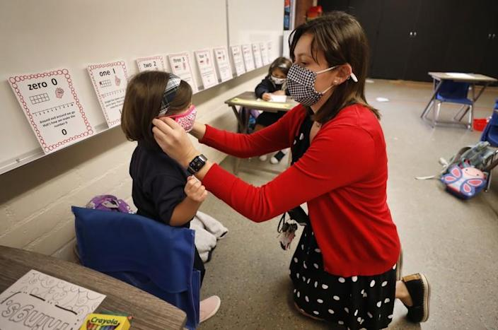 LONG BEACH, CA - OCTOBER 26: Transitional kindergarten and kindergarten teacher Heather Hernandez helps Amelia Dunn with her mask in the classroom as roughly 40 students returned to St. Maria Goretti Catholic School in Long Beach for in-person instruction Monday with transitional kindergarten and kindergarten returning for full-time in-person instruction and 1st and 2nd grade students adopting a hybrid schedule. St. Maria Goretti is the first Catholic School in Los Angeles County to receive waiver approval to reopen since schools moved to remote learning in March due to the COVID-19 pandemic. St. Maria Goretti Catholic School on Monday, Oct. 26, 2020 in Long Beach, CA. (Al Seib / Los Angeles Times