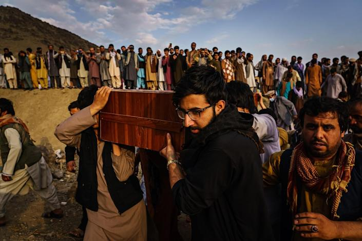 Caskets of the dead are carried at a mass funeral for civilians killed in a U.S. drone strike in August.